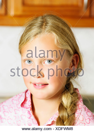 Young girl in kitchen looking at camera. - Stock Photo