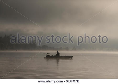 Fisherman early in the morning with fog in the morning light on Weissensee lake, Carinthia, Austria, Europe - Stock Photo