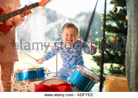 Boy and sister playing toy drum kit and guitar on christmas day - Stock Photo