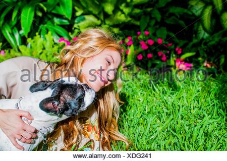 Dog licking woman's face in garden - Stock Photo