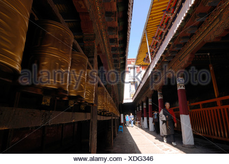 Tibetan prayer wheels, prayer cylinders, and Buddhist pilgrims, elderly man, in the course of the circumnavigation of Jokhang T - Stock Photo
