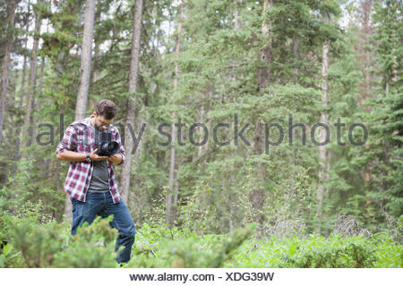 Male photographer using an SLR camera outdoors - Stock Photo