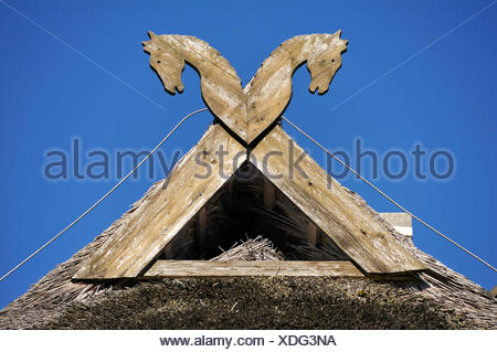 Horses, the heraldic animals of Lower Saxony, on a gable with an owl's nest against a blue sky, Haferland Hotel and Restaurant - Stock Photo