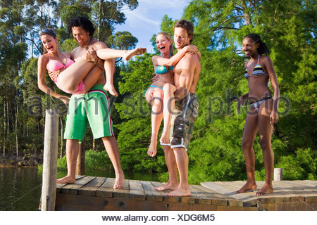 Two young men throwing female friends in bikinis from jetty into lake laughing - Stock Photo