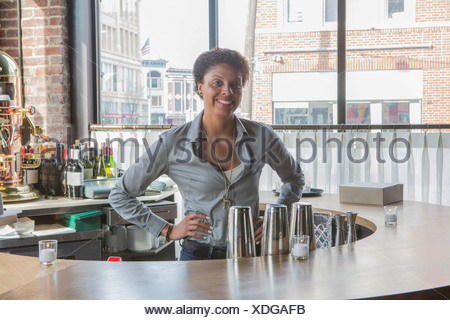 Portrait of waitress behind restaurant bar - Stock Photo