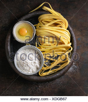 Raw uncooked homemade italian pasta tagliatelle with pasta cutter, bowls with white flour and broken egg in old clay tray over d - Stock Photo
