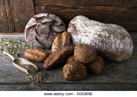 Bread loaves, rolls with rye grain and ears of corn on a rustic wooden surface - Stock Photo