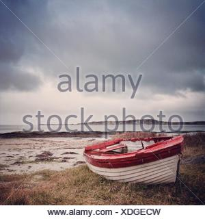 UK, Scotland, Inner Hebrides, Jura, Red and white boat on grass - Stock Photo