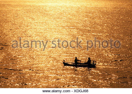 Two people in a rowboat on the Sorpesee lake at sunset, Sunderland, Hochsauerlandkreis district, North Rhine-Westphalia - Stock Photo