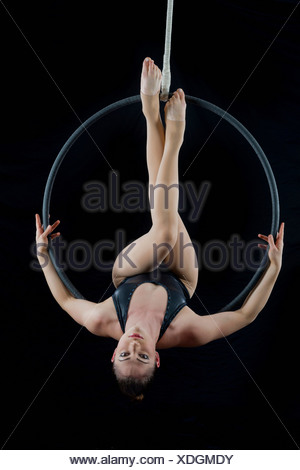 Aerialist performing on hoop in front of black background - Stock Photo