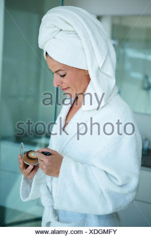 woman wearing a dressing gown holding face powder - Stock Photo