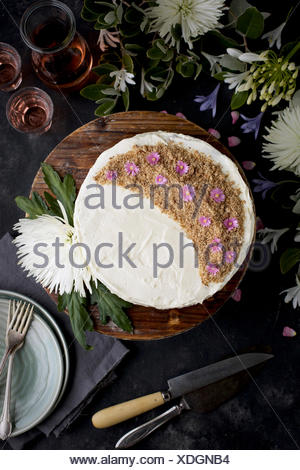 Marzipan Almond Cake with a Orange Blossom Mascarpone Frosting on a wooden pedestal, served with Rosé wine.  Photographed on a black/gray background. - Stock Photo