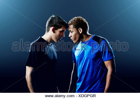 Portrait of two male soccer players head to head - Stock Photo
