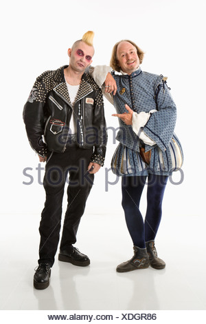 William Shakespeare smiling and leaning on gothic punk young man looking at viewer - Stock Photo