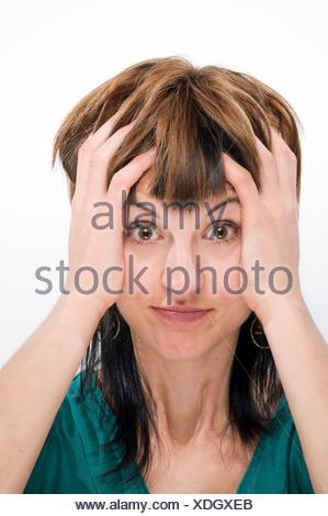 Kopf-und-Schulter-Aufnahme einer jungen sich die Haare raufenden Frau mit Blick in die Kamera - Stock Photo