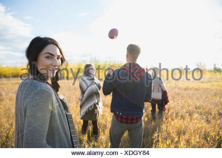 Portrait smiling young woman with friends in sunny field - Stock Photo