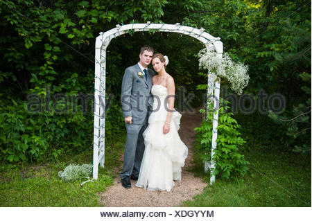 A bride and groom stand under an archway on their wedding day. - Stock Photo