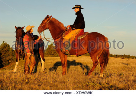 Cowgirl and cowboy with horses in the evening sun, Saskatchewan, Canada, North America - Stock Photo