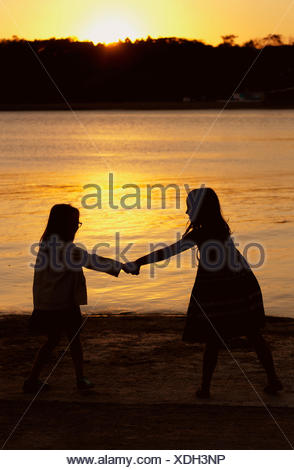 Silhouette of  Two girls holding hands at  sunset - Stock Photo