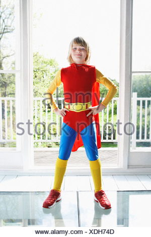Portrait of young boy (7-9) posing in superhero costume with hands on hip - Stock Photo