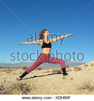 Woman doing a warrior pose, Nevada, America, USA - Stock Photo