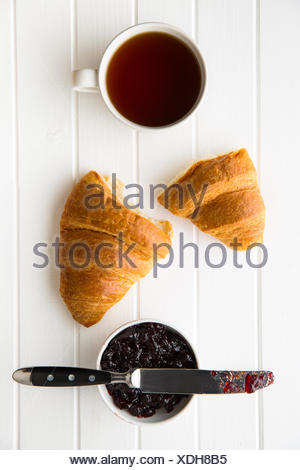 Tasty buttery croissant, cup of black tea and jam in jar. - Stock Photo