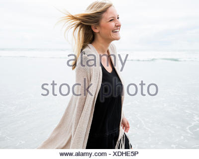 Portrait of a smiling young woman on a beach - Stock Photo