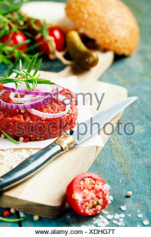 Raw beef burger for hamburger with vegetables on wooden table - Stock Photo