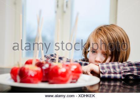 Girl (6-7) looking at taffy apples - Stock Photo