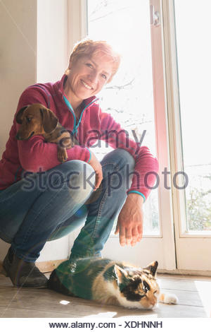 Mature woman with her pets at home, Bavaria, Germany - Stock Photo