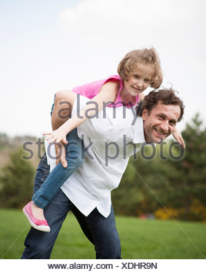 Father giving young daughter piggyback ride - Stock Photo