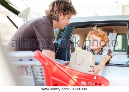 Father and son loading groceries in car - Stock Photo