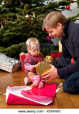 father, baby opening christmas present - Stock Photo