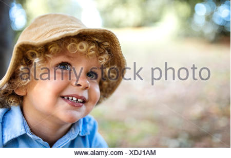 Portrait of smiling blond little boy wearing hat - Stock Photo