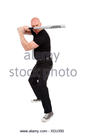 bald headed man with baseball bat in front of his face is looking angry into the camera - Stock Photo