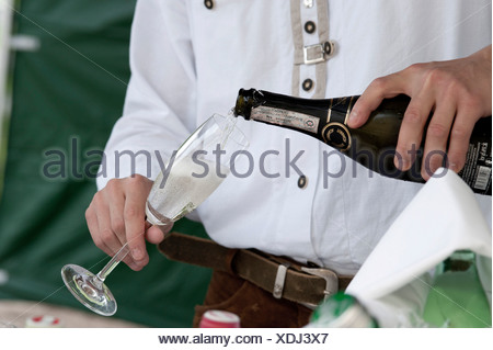 Man pouring a glass of champagne, sparkling wine or prosecco, close-up of hands - Stock Photo