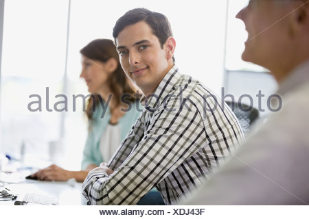 Portrait of businessman sitting with colleagues in office - Stock Photo