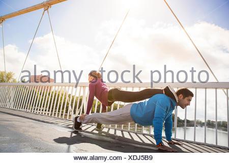 Young couple performing push-ups, man backing woman, Osijek, Croatia - Stock Photo