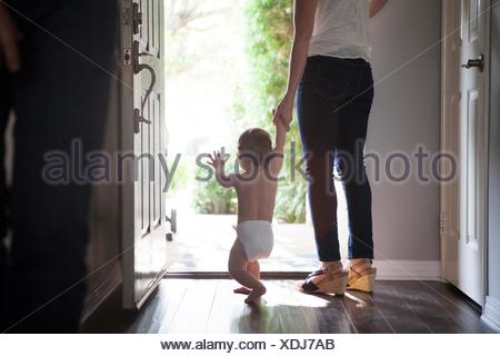 Rear view of mother holding baby boys hands standing at open front door - Stock Photo