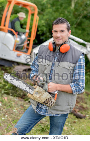 Landscape gardener with a chainsaw - Stock Photo