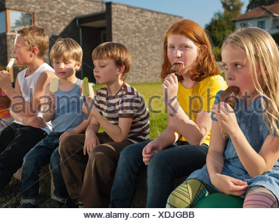 Friends sitting on sidewalk and  enjoying ice loliies, portrait - Stock Photo