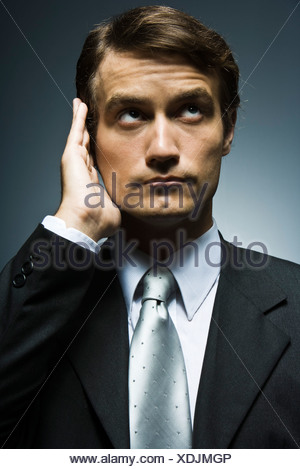 Businessman with hand cupped around ear listening attentively - Stock Photo