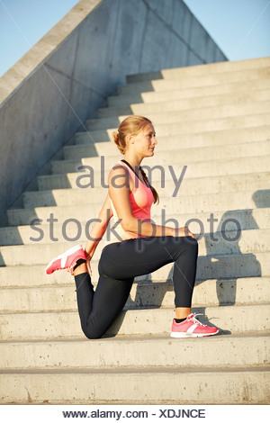 Runner stretching on staircase - Stock Photo