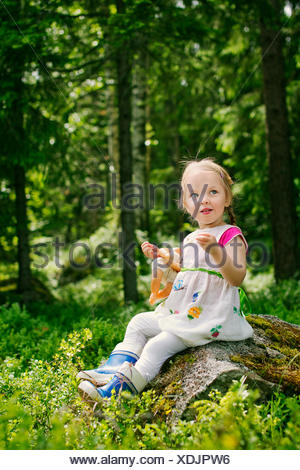 Finland, Paijat-Hame, Girl (2-3) playing with doll in forest - Stock Photo