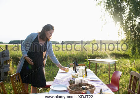 Pregnant woman setting the table for garden party dinner in sunny summer rural yard - Stock Photo