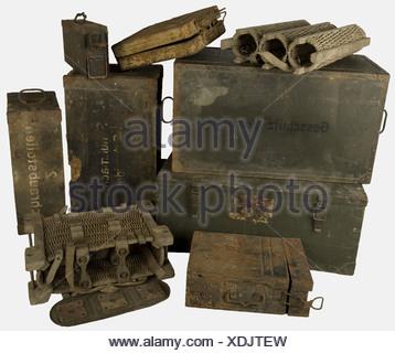 ACCESSOIRES, Ensemble de caisses allemandes, comprenant une valise en tôle nervurée peinte sable pour obus de mortier lourd de 8 cm sans ses compartiments internes de calage, un panier en osier à 3 compartiments cylindriques pour trois obus de 7,7 cm sans couvercle, un panier complexe à deux cotés pour 6 douilles d'artillerie à construction en vannerie, bois tôle, cuir et sangles (un couvercle absent), une caissette en tôle d'acier pour une bande de mitrailleuse M.G. 34/42 (oxydée), une caisse en bois feldgrau à couvercle articulé et poignées fil de fer marquée, Additional-Rights-Clearances-NA - Stock Photo