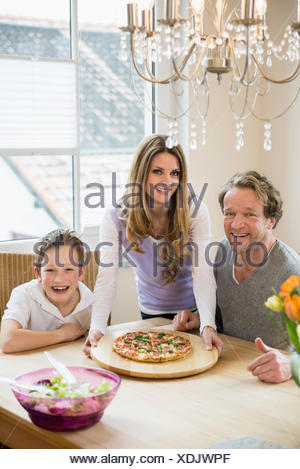 Family eating pizza and salad at home - Stock Photo