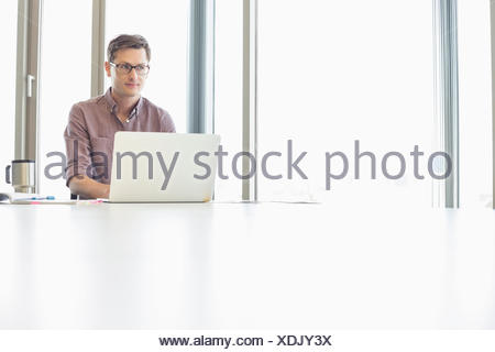 Thoughtful businessman looking away while using laptop at desk in creative office - Stock Photo