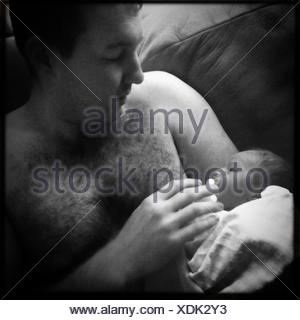 Father Holding Newborn Baby In Arms - Stock Photo