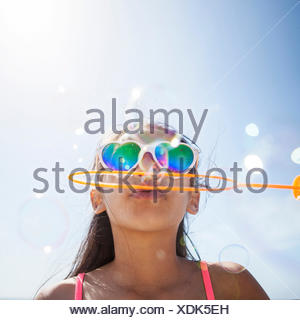 Girl in heart shaped sunglasses on beach blowing bubbles with bubble wand - Stock Photo